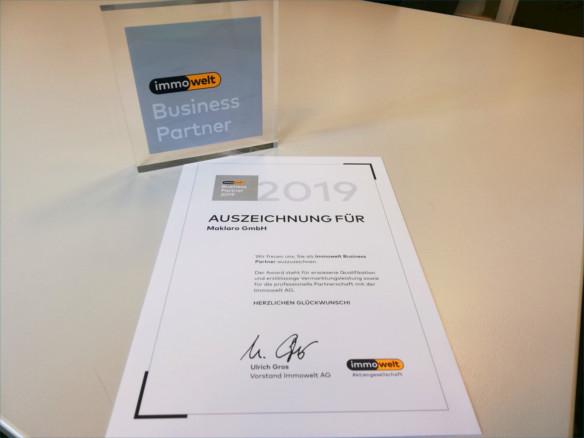 Urkunde und Award Immowelt Business Partner auf Tisch